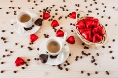 Red chocolate hearts in a small basket and two cups of coffee - stock photo
