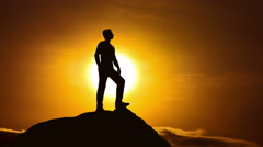 The man stand on a cliff on the background of sunset. Real time capture - stock footage