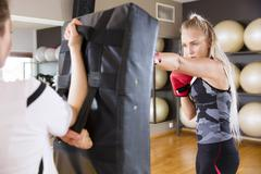 Two focused women boxing at the gym Stock Photos