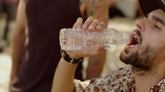 Man passing the water bottle to his friend after drinking the water Stock Footage