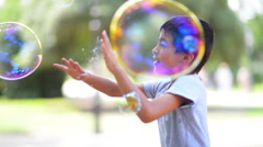 Boy catching soap bubbles in a summer day Stock Footage