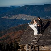 Beautiful wedding couple on the roof of country house. Breathtaking mountain - stock photo