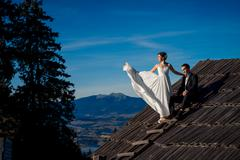 Beautiful wedding couple posing on the top of  roof. Amazing mountain landscape Stock Photos