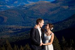 Bride and groom happily smiling. Amazing mountains view on background Stock Photos