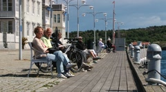 People relax at the sea side street in the town of Smogen, Sweden. Stock Footage