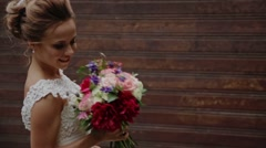 Bride smiles and holds flowers in hands Stock Footage
