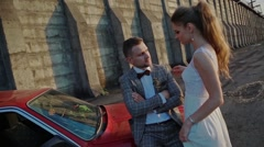 Newlyweds on the background of a dam and a red car Stock Footage