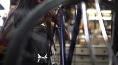 Woman bicycle mechanic fixing a wheel in a repair workshop - stock footage