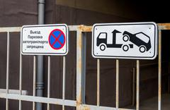Traffic sign prohibiting parking mounted on metal gate. Evacuation on tow tru - stock photo