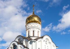 Golden dome of Russian orthodox church with cross against blue sky - stock photo