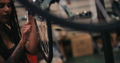 Tattooed female bicycle mechanic working in a repair shop Stock Footage