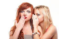 Stock Photo of society gossip - two happy young girlfriends talking white background