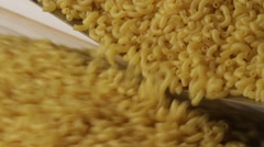 Close up shot of macaroni dropping from a machinery to prepare pasta - stock footage