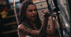 Woman bicycle mechanic with dreadlocks working in bike repair workshop Stock Footage