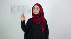Young Muslim girl in black dress touching virtual screen / technological display Stock Footage
