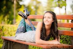 Beautiful brunette lies on bench - stock photo