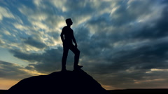 The man stand against the move clouds. Time lapse. Wide angle - stock footage