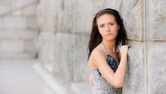 Beautiful girl about stone wall - stock photo