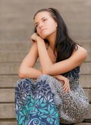 Young beautiful girl sits on steps - stock photo