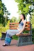 Beautiful brunette sits on bench - stock photo