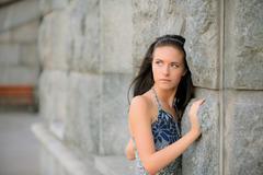 Beautiful girl about stone wall - stock photo