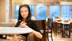 Charming young woman eats dessert - stock photo
