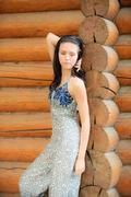 Beautiful brunette at log hut - stock photo