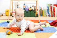Baby first crawling attempts - stock photo