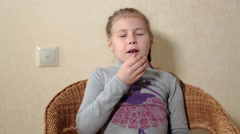 Little girl sitting in the chair at home and sneezing, covering her mouth Stock Footage