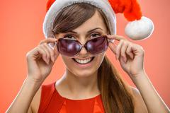 woman in Santa Claus clothes with sunglasses - stock photo