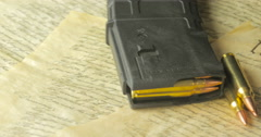 Stock Video Footage of Panning Shot of Ammunition Lying on the Constitution of the USA