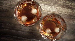 Glasses of whiskey with ice on wooden table. Stock Footage