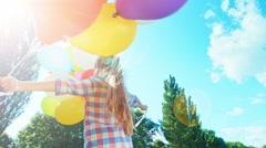 Girl 6-8 years spinning with balloons against the sky in the sunlight. Sunlight Stock Footage