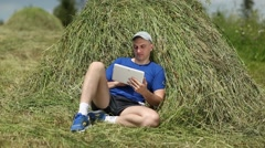 Man with tablet PC lies on a haystack Stock Footage