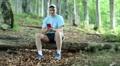 Man with red smartphone sits on a fallen tree in the forest Footage