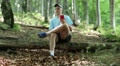 Man with red smartphone sits on a fallen tree in forest and listens to music Footage