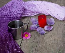 Lilac scarf, mug, red candle and petals Stock Photos