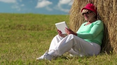 Blonde woman sits on a green grass near haystack and communicates via tablet PC Stock Footage