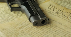 Panning Shot of a Handgun Lying on the United States Constitution Stock Footage