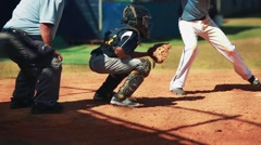 An umpire, catcher and batter in the middle of a play during baseball game. - stock footage