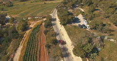 Aerial Shot - Following a Red Car driving by the fields Stock Footage