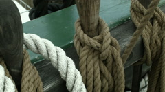 A top to bottom panning shot of a sailing ship's deck rail with ropes Stock Footage