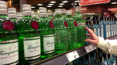 A hand takes bottle of UK Tanqueray No ten batch distilled from the shelf - stock footage