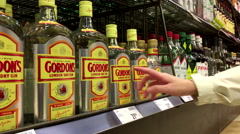 A hand takes bottle of Gordon's London dry gin from the shelf - stock footage