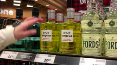 A hand takes bottle of Ungava canadian premium gin from the shelf - stock footage
