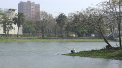 4k, Old Asian fisherman fishing on paceful lake in the Kaohsiung city-Dan Stock Footage