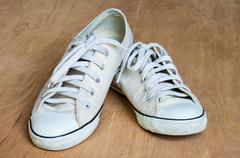 White sneaker on wood background - stock photo