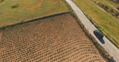 Aerial Shot - Following a Car driving near green fields Stock Footage