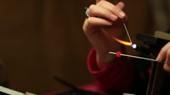 Women's hands make glass beads Stock Footage