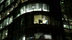 MAN IN ILLUMINATED LONDON OFFICE WINDOW PUTS ON OVERCOAT Stock Footage